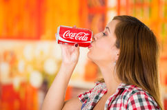 Quito, Ecuador - May 06, 2017: Beautiful young woman drinking a coke in a blurred background.  Royalty Free Stock Photos