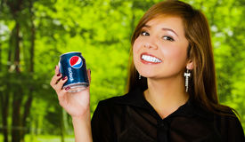 Quito, Ecuador - May 06, 2017: Smiling pretty young woman holding a pepsi in blurred green background Stock Photo
