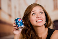 Quito, Ecuador - May 06, 2017: Smiling young woman holding a pepsi in blurred city background Stock Photos