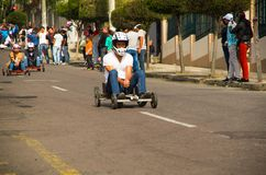 Quito, Ecuador - May 06, 2017: An unidentified man racing a wooden car in an urban road inside of the streets of city of. Quito Royalty Free Stock Images