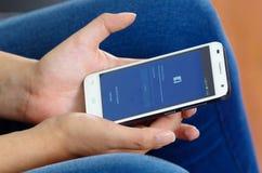 Quito, Ecuador - Mei 09, 2017: Vrouw met moderne mobiele telefoon in handenlogin het scherm facebook pictogrammen op Apple-iPhone Stock Afbeelding
