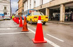 QUITO, ECUADOR NOVEMBER, 28, 2017: Close up of orange cones in the historical center, with some cars parked in the Stock Photos