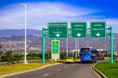 Quito Ecuador - November 23 2017: Några bilar som cirkulerar under ett informativt tecken av Quitoflygplatsmitten som över lokali Arkivfoton