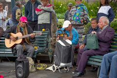 QUITO, ECUADOR NOVEMBER, 28, 2017: Outdoor view of some old musician people sitting in a public chair, playing some. Music at historical center of old town Royalty Free Stock Photo