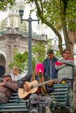QUITO, ECUADOR NOVEMBER, 28, 2017: Outdoor view of some old musician people sitting in a public chair, playing some. Music at historical center of old town Stock Image