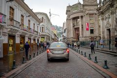 QUITO, ECUADOR NOVEMBER, 28, 2017: Unidentified people walking at historical center with some cars in the streets of old. Town Quito in northern Ecuador in the Stock Photo