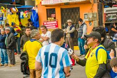QUITO, ECUADOR - OCTOBER 11, 2017: Close up of reporter talking to some Argentina fans surrounding with a crowd of. People wearing official football shirt stock images