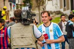 QUITO, ECUADOR - OCTOBER 11, 2017: Close up of reporter talking to some ecuadorian fans surrounding with a crowd of. People wearing official Marathon football royalty free stock image