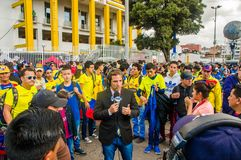 QUITO, ECUADOR - OCTOBER 11, 2017: Close up of reporter talking to some ecuadorian fans surrounding with a crowd of. People wearing official Marathon football stock photos
