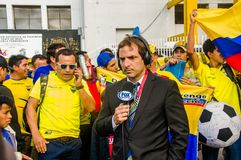 QUITO, ECUADOR - OCTOBER 11, 2017: Close up of reporter talking to some ecuadorian fans surrounding with a crowd of. People wearing official Marathon football royalty free stock photo