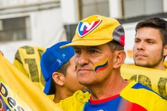 QUITO, ECUADOR - OCTOBER 11, 2017: Portrait of old man wearing a yellow hat with his face painted with the colors of Stock Photography