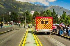 QUITO, ECUADOR - OKTOBER 23, 2017: Niet geïdentificeerde mensen die die in de straten met een ziekenwagen lopen in de straat word royalty-vrije stock afbeelding