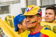 QUITO, ECUADOR - 11. OKTOBER 2017: Porträt des alten Mannes einen gelben Hut mit seinem Gesicht tragend gemalt mit den Farben von Stockfotografie