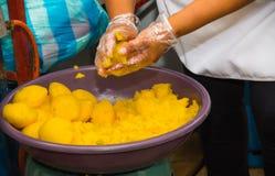 Quito, Ecuador, 26,2017 Oktober: Vrouw die keukenhandschoenen dragen en de massa van Gebroken aardappel behandelen, om a voor te  Stock Foto's