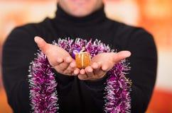 QUITO, ECUADOR 17 OTTOBRE 2015: Chiuda su di una tenuta del giovane in sue mani un regalo e un albero di Natale variopinto Immagine Stock