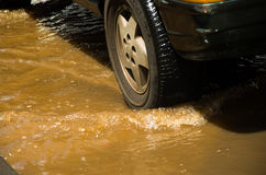QUITO, ECUADOR - SEPTEMBER 20, 2016: Close up of a neumatic car rides on a flooded road in Quito city after a heavy rain Stock Images