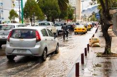 QUITO, ECUADOR - SEPTEMBER 20, 2016: Een motocycle en een auto berijden op een overstroomde weg in Quitostad na een zware regen Royalty-vrije Stock Foto