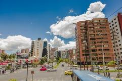 QUITO ECUADOR - SEPTEMBER 10, 2017: Oidentifierat folk som går, och siktstrafik med några bilar som between cirkulerar Arkivbild