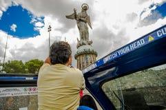 QUITO ECUADOR - SEPTEMBER 10, 2017: Unidentifed kvinna som tar bilder av panecillostatyn och tycker om det härligt Royaltyfri Bild