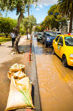 QUITO, ECUADOR - SEPTEMBER 20, 2016: An unidentified people walk in the sidewalk while some cars rides on a flooded road Royalty Free Stock Photo