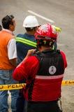 Quito Ekwador, Grudzień, - 09, 2016: Niezidentyfikowana grupa strażaka ` s mężczyzna czekanie za niebezpieczeństwo taśmą w ulicac Obrazy Stock