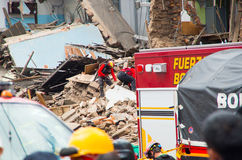 Quito Ekwador, Grudzień, - 09, 2016: Niezidentyfikowani firemans w całkowicie rujnującym ceglanym domu w Quito mieście z Zdjęcia Stock