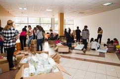 Quito Ekwador, Kwiecień, - 23, 2016: Niezidentyfikowani mieszkanowie providing pomocy ofiarom klęsk jedzenie Quito, odziewają, me Zdjęcia Royalty Free