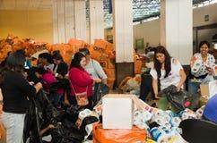 Quito Ekwador, Kwiecień, - 23, 2016: Niezidentyfikowani mieszkanowie providing pomocy ofiarom klęsk jedzenie Quito, odziewają, me Zdjęcie Stock