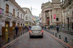 QUITO, EKWADOR LISTOPAD, 28, 2017: Niezidentyfikowani ludzie chodzi przy dziejowym centrum z niektóre samochodami w ulicach stary Zdjęcie Stock