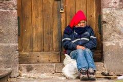 QUITO, EKWADOR LISTOPAD, 28, 2017: Niezidentyfikowany bezdomny mężczyzna w chodniczku przy dziejowym centrum stary grodzki Quito  Obrazy Stock