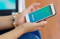 Quito Ekwador, Maj, - 09, 2017: Kobieta z nowożytnym telefonem komórkowym w ręki nazwy użytkownika ekranu świergotu ikonach na Ja Obrazy Stock