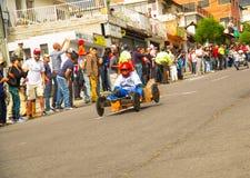 Quito Ekwador, Maj, - 06, 2017: Niezidentyfikowana chłopiec ściga się drewnianego samochód w ulicach miasto Quito Zdjęcie Stock