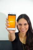 Quito Ekwador, Maj, - 09, 2017: Piękna kobieta z nowożytnym telefonem komórkowym w rękach, nazwa użytkownika ekranu FOX sztuka na Obrazy Royalty Free