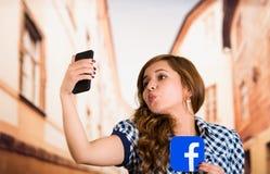Quito Ekwador, Marzec, - 11, 2016: Kobieta bierze selfie z nowożytnym telefonem komórkowym i trzyma majcheru facebook ikonę Obraz Stock