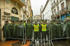 Quito Ekwador, Sierpień, - 27, 2015: Policjanci za metalem fechtują się barrricade oczekuje rozkazy podczas masowych demonstracj Obraz Stock