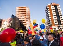 Quito, Equador - 7 de abril de 2016: Grupo de pessoas que guarda sinais do protesto, balões com polícia e journalistas durante an Fotos de Stock Royalty Free