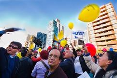 Quito, Equador - 7 de abril de 2016: Grupo de pessoas que guarda sinais do protesto, balões com polícia e journalistas durante an Imagens de Stock