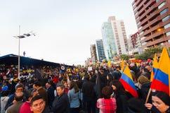 Quito, Equador - 7 de abril de 2016: Grupo de pessoas que guarda sinais do protesto, balões com polícia e journalistas durante an Fotografia de Stock