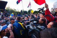 Quito, Equador - 7 de abril de 2016: Grupo de pessoas que guarda sinais do protesto, balões com polícia e journalistas durante an Imagens de Stock Royalty Free