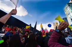 Quito, Equador - 7 de abril de 2016: Grupo de pessoas que guarda sinais do protesto, balões com polícia e journalistas durante an Fotografia de Stock Royalty Free