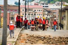 Quito, Equador - 9 de dezembro de 2016: Um grupo não identificado de firemans, com os materiais de uma construção para limpar o d Imagem de Stock