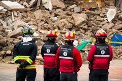Quito, Equador - 9 de dezembro de 2016: Um grupo não identificado de firemans que olha o dano e a destruição na construção Imagem de Stock Royalty Free