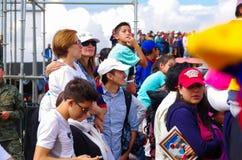 QUITO, EQUADOR - 7 DE JULHO DE 2015: Adultos, mulher e homens, pagando a atenção à massa do papa Francisco, dia ensolarado Fotos de Stock