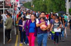QUITO, EQUADOR - 7 DE JULHO DE 2015: A família que andam na rua, a mãe, o pai e a criança pequena querem ver o papa Francisco Imagem de Stock
