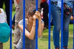 QUITO, EQUADOR - 7 DE JULHO DE 2015: Moça que reza na massa do papa Francisco em Equador, nos olhos fechados e na cabeça para bai Imagem de Stock