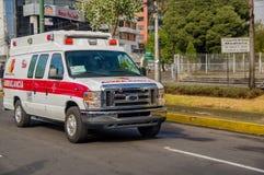 QUITO, EQUADOR - 7 DE JULHO DE 2015: Vadear a ambulância branca com os detalhes vermelhos que cruzam a cidade, emergências soment foto de stock