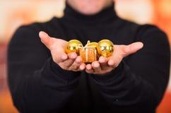 QUITO, EQUADOR 17 DE OUTUBRO DE 2015: Feche acima de um homem novo que realiza em suas mãos um presente dourado e uma árvore de N Fotografia de Stock