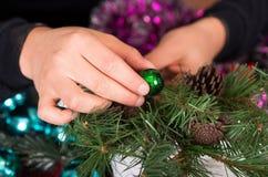 QUITO, EQUADOR 17 DE OUTUBRO DE 2015: Feche acima de um homem novo que realiza suas mãos em uma árvore de Natal bonita e colorida Imagens de Stock