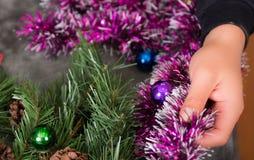 QUITO, EQUADOR 17 DE OUTUBRO DE 2015: Feche acima de um homem novo que realiza suas mãos em uma árvore de Natal bonita e colorida Fotografia de Stock