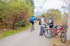 QUITO, EQUADOR - MARZO 23, 2015: Os pares não identificados param para arranjar o equipamento de um ciclista Imagem de Stock